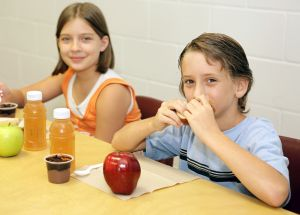 A boy and girl eating a healthy lunch together in school.